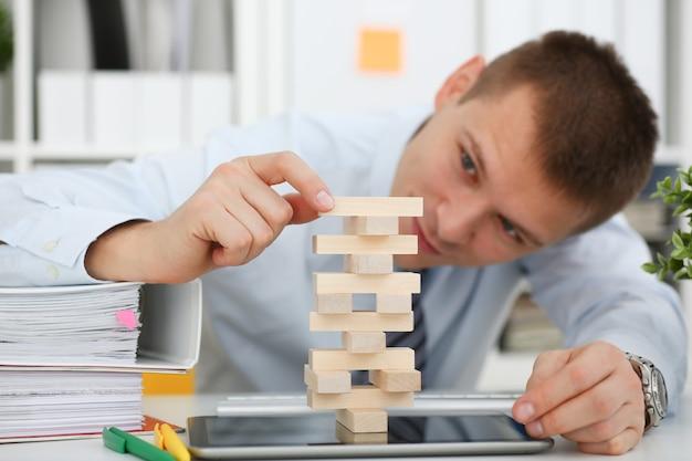 Geschäftsmann spielt in der strategiehand, welche die holzklötze neu ordnet, die während des bruches bei der arbeit im sitzenden tabellenspielstapelspaß-freuden-zeitvertreibkonzept des büros mit einbezogen werden