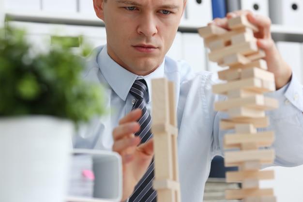 Geschäftsmann spielt in einer strategie der jenga-hand