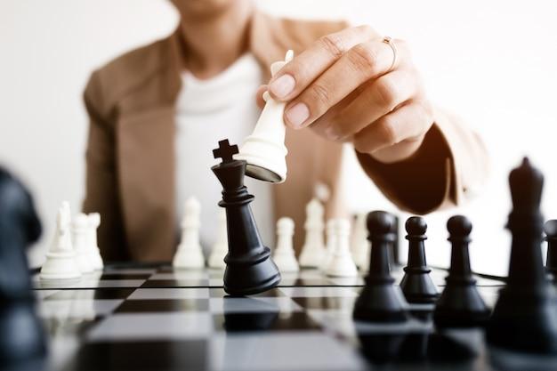 Geschäftsmann spielt schach an bord in büro, strategie und wettbewerb konzept