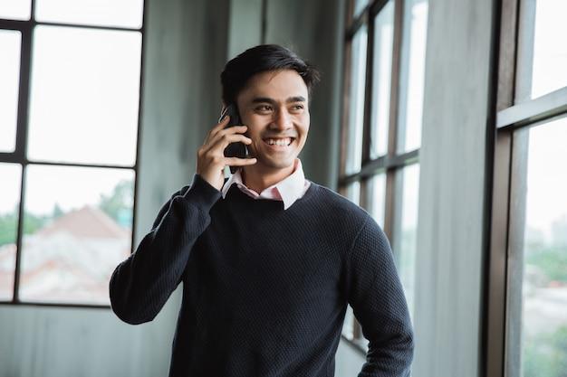 Geschäftsmann spricht auf seinem smartphone und schaut zum fenster