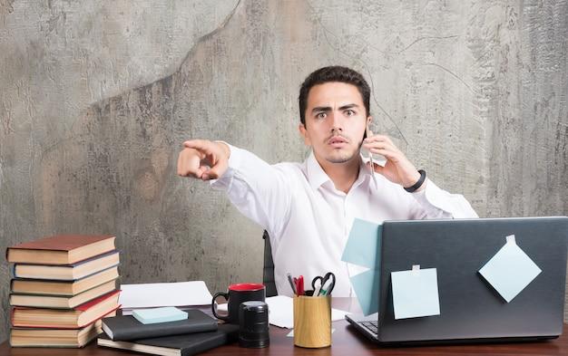 Geschäftsmann spricht mit telefon und zeigt nach vorne auf den schreibtisch.