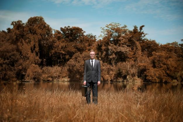 Geschäftsmann standing field brown grass concept