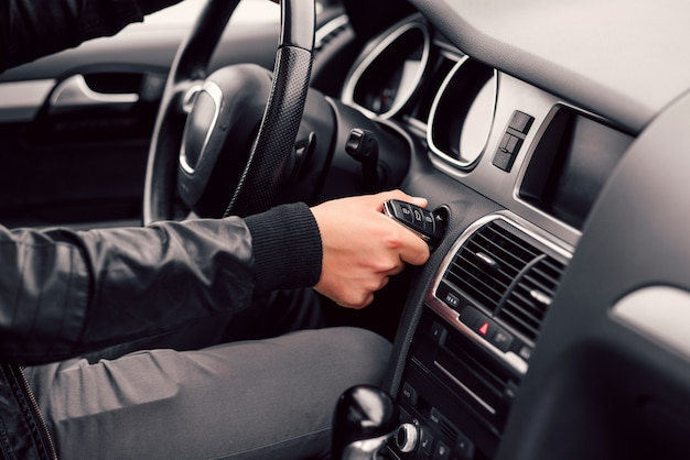 Geschäftsmann startet sein stilvolles modernes auto mit dem schlüssel