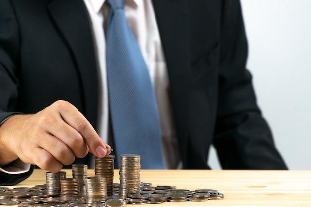Geschäftsmann steckte münzenstapelgeld