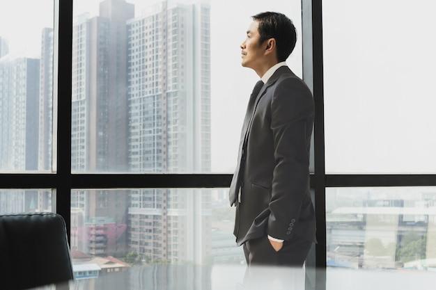 Geschäftsmann steht neben dem fenster mit blick auf die seitenansicht Premium Fotos