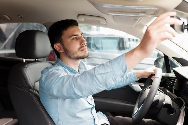 Geschäftsmann stellt den rückspiegel in seinem auto ein