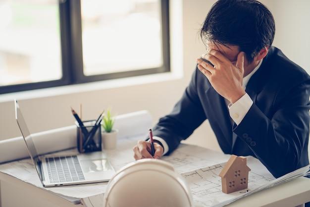 Geschäftsmann stress und sorgen über die späte zeit bis zum abschluss des bauprojekts