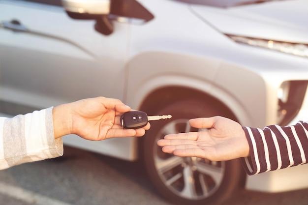 Geschäftsmann tauscht die übergabe der autoschlüssel an eine junge frau aus.