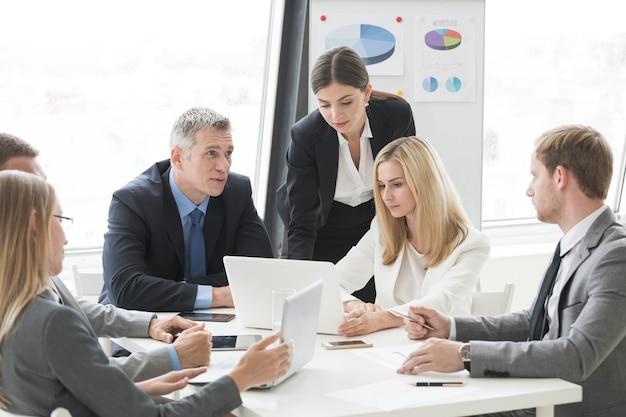 Geschäftsmann-team beim treffen im büro, das mit diagrammen und diargams arbeitet