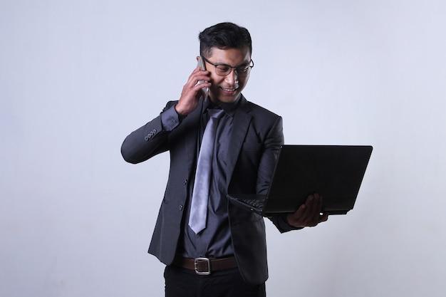Geschäftsmann telefoniert beim lächeln und betrachten des laptops