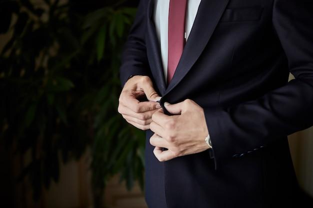Geschäftsmann trägt eine jacke, männliche hände nahaufnahme, bräutigam, der sich am morgen vor der hochzeitszeremonie fertig macht