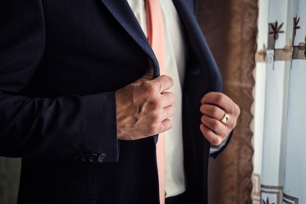 Geschäftsmann trägt eine jacke. politiker, männerstil, männliche hände nahaufnahme, geschäftsmann, geschäft, mode und kleidungskonzept