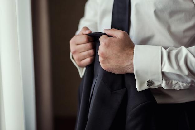 Geschäftsmann trägt eine jacke. politiker, männerstil, männliche handnahaufnahme, amerikanischer, europäischer geschäftsmann, geschäfts-, mode- und bekleidungskonzept