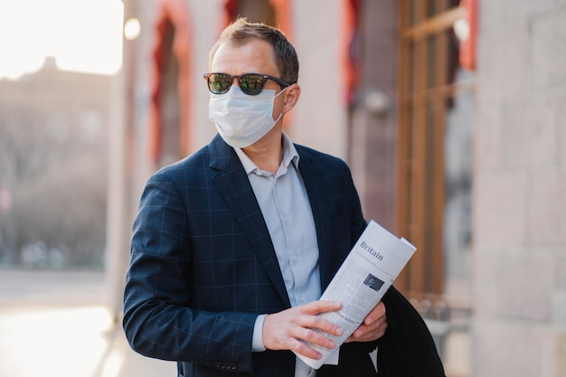 Geschäftsmann trägt schutzmaske gegen übertragbare infektionskrankheiten, liest zeitungen