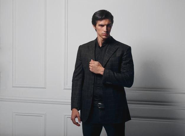 Geschäftsmann tragen schwarzes anzugporträt gegen einen dunklen hintergrund, der die seite betrachtet. nahaufnahmeporträt eines gutaussehenden mannes. horizontale ansicht.