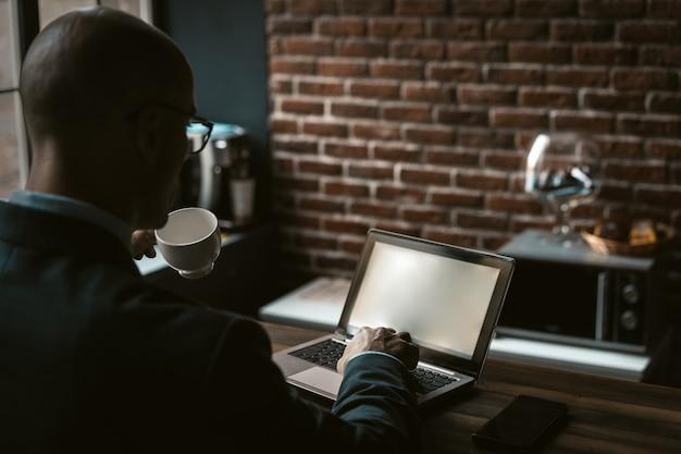 Geschäftsmann trinkt kaffee, der mit computer im geschäftszentrum arbeitet. rückansicht des kaukasischen mannes