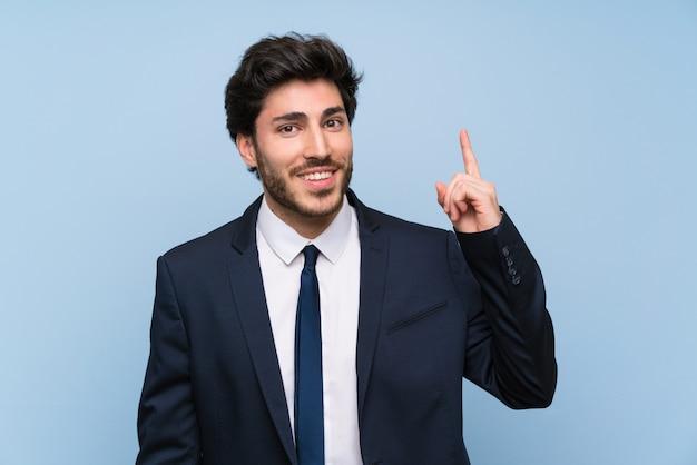 Geschäftsmann über der lokalisierten blauen wand, die beabsichtigt, die lösung beim anheben eines fingers zu verwirklichen