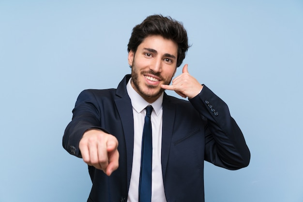 Geschäftsmann über der lokalisierten blauen wand, die telefongeste macht und front zeigt