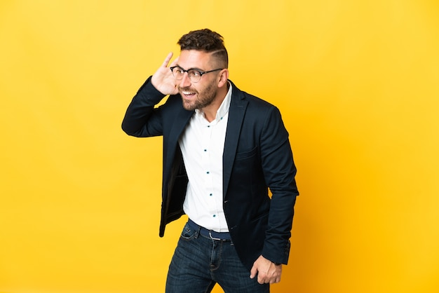 Geschäftsmann über isoliertem gelbem hintergrund, der etwas hört, indem er die hand auf das ohr legt