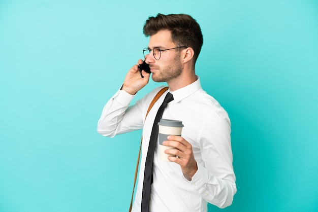 Geschäftsmann über isoliertem hintergrund mit kaffee zum mitnehmen und einem handy