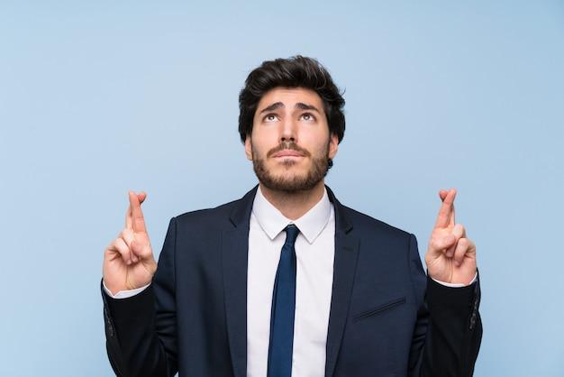 Geschäftsmann über lokalisierter blauer wand mit den fingern, die das beste kreuzen und wünschen