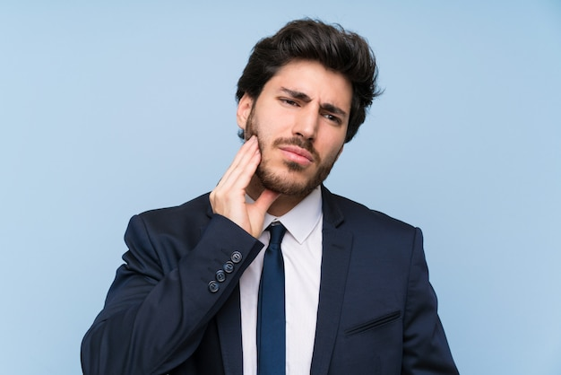 Geschäftsmann über lokalisierter blauer wand mit zahnschmerzen