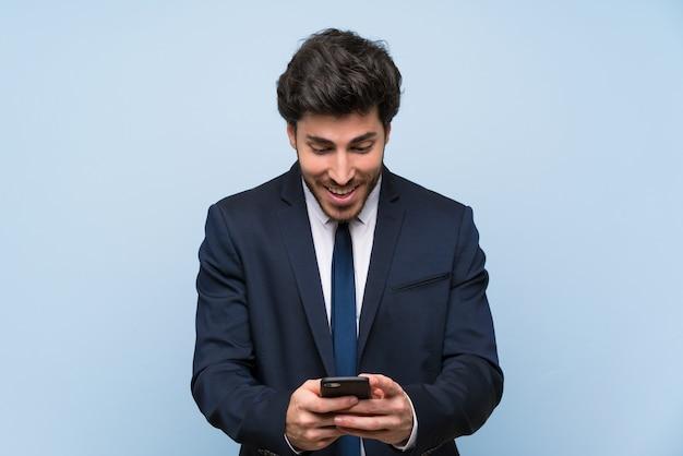 Geschäftsmann über lokalisierter blauer wand überrascht und eine mitteilung sendend