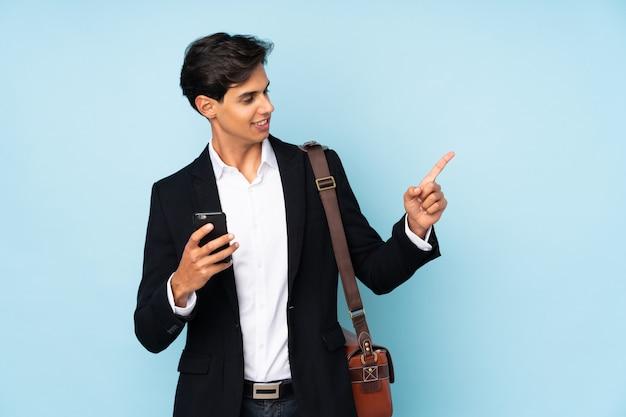 Geschäftsmann über lokalisierter blauer wand überrascht und finger auf die seite zeigend