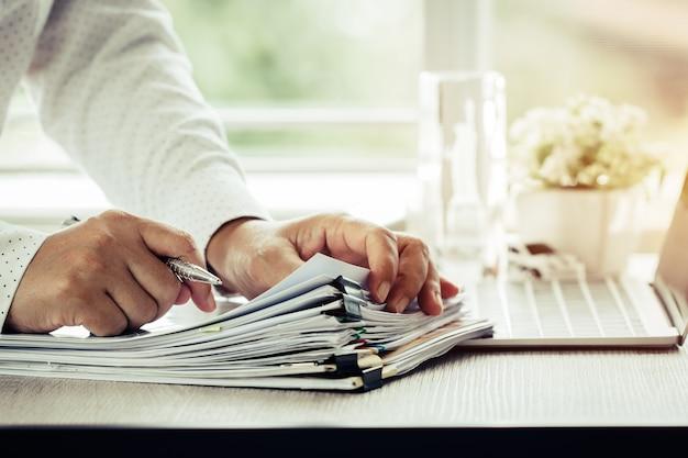 Geschäftsmann übergibt das halten für das arbeiten in den stapeln papierakten information r suchend
