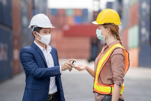 Geschäftsmann und arbeiter tragen eine medizinische maske mit alkoholgel zur handreinigung.