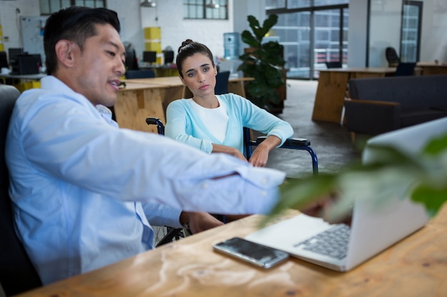 Geschäftsmann und behinderte frau diskutieren über laptop