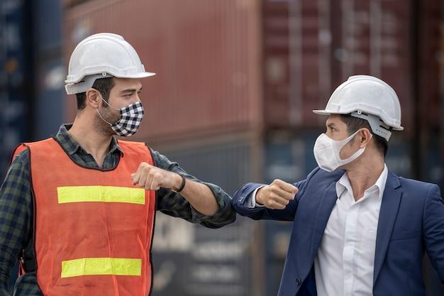 Geschäftsmann und fabrikarbeiter, die in einer medizinischen maske und sicherheit tragen
