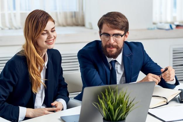 Geschäftsmann und frau arbeiten zusammen vor laptop-profis-technologie