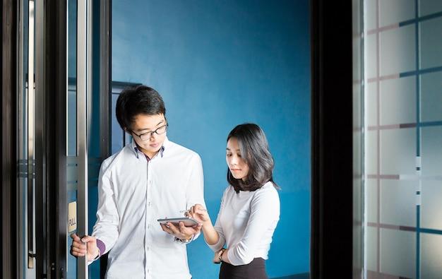 Geschäftsmann und frau besprechen sich mit tablette über ihre arbeit in der halle des büros