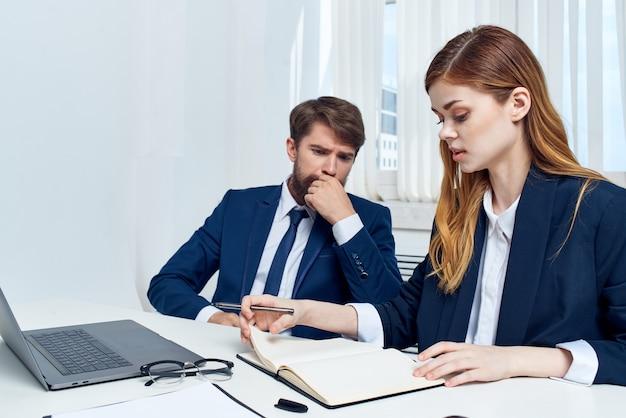 Geschäftsmann und frau chatten im büro vor einer laptop-technologie