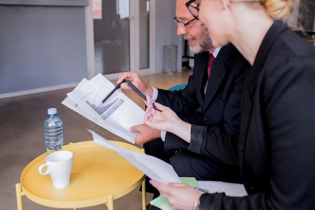 Geschäftsmann und frau, die am schreibtisch spricht und über berichte und finanzen sitzen