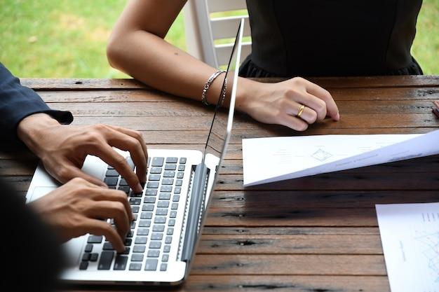 Geschäftsmann und frau, die an berichtspapier büro im im freien mit kommunikationsgang arbeiten