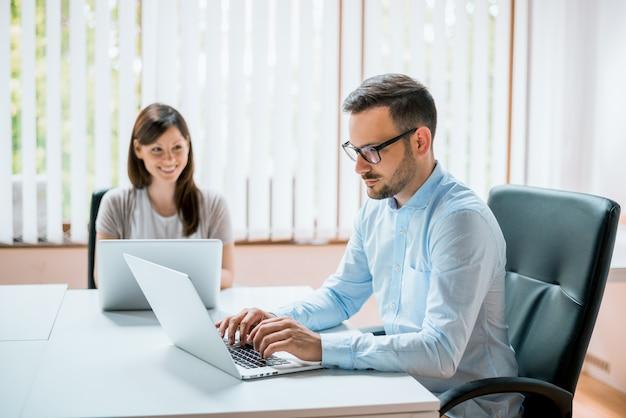Geschäftsmann und frau, die an ihren computern arbeiten.
