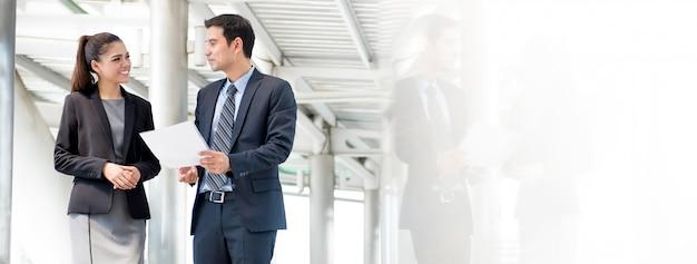 Geschäftsmann und frau, die arbeit unterwegs besprechen