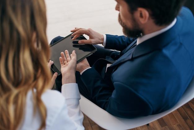 Geschäftsmann und frau, die die teamarbeit der tablet-beamten betrachten