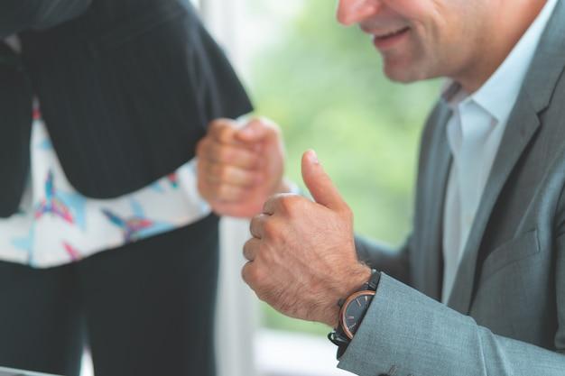 Geschäftsmann und frau, die sich daumen für teamerfolg zeigen