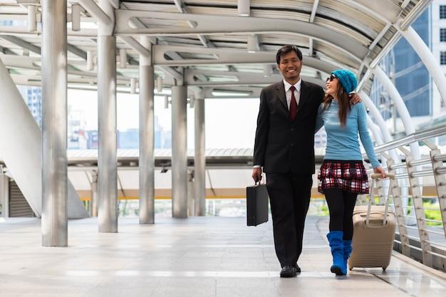 Geschäftsmann und -frau halten reisegepäckweg durch passagierwegweg.