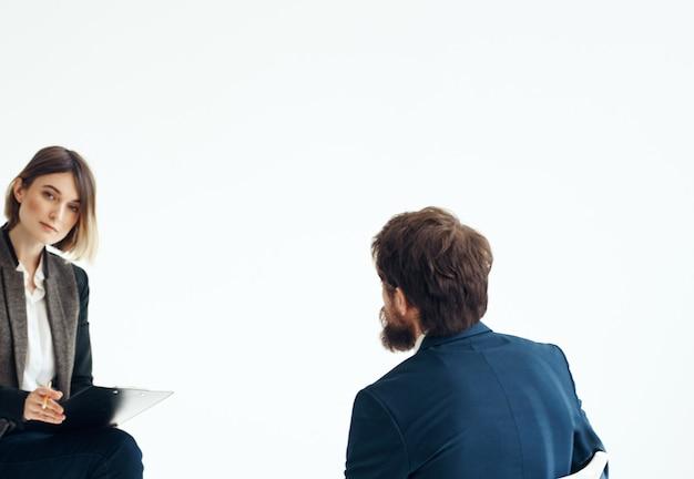 Geschäftsmann und frau im anzug auf einem hellen hintergrundkommunikationspersonal-vorstellungsgespräch