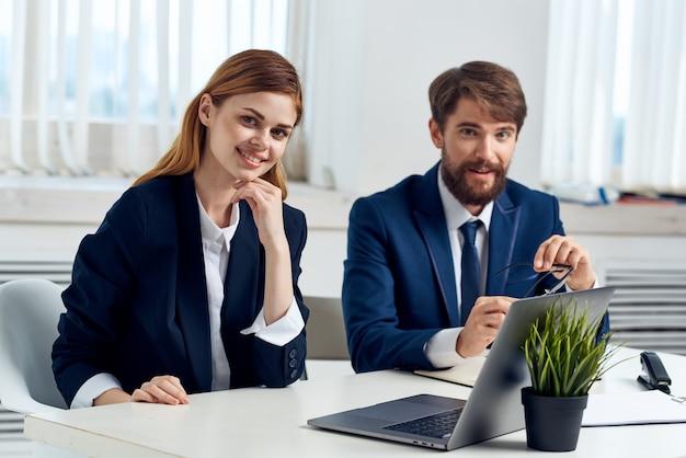 Geschäftsmann und frau sitzen am tisch vor laptop-team-technologie. foto in hoher qualität