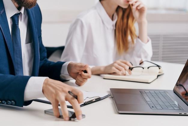 Geschäftsmann und frau sitzen am tisch vor laptop-team-technologie