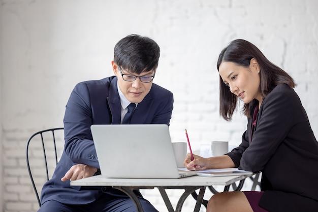 Geschäftsmann und frau sitzen an einem tisch und schauen auf computer-laptop