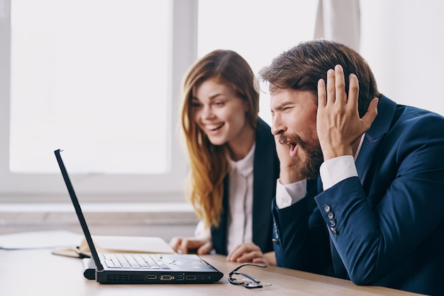 Geschäftsmann und frau sitzen vor einem laptop teamwork-profis