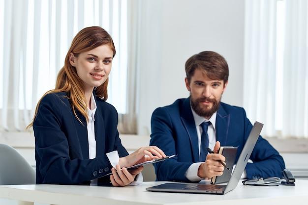Geschäftsmann und frau sprechen am tisch vor laptop-bürotechnik