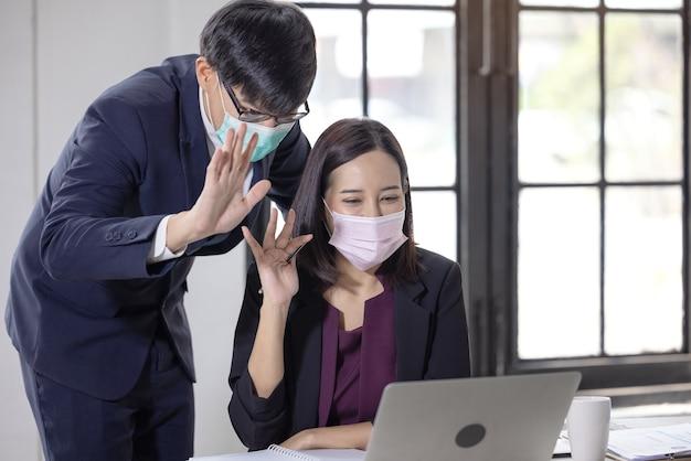 Geschäftsmann und frauen, die gesichtsmasken tragen, während sie laptop verwenden und jemanden während des videoanrufs im büro begrüßen. konferenz mit arbeitsteam inmitten der covid-19-pandemie.