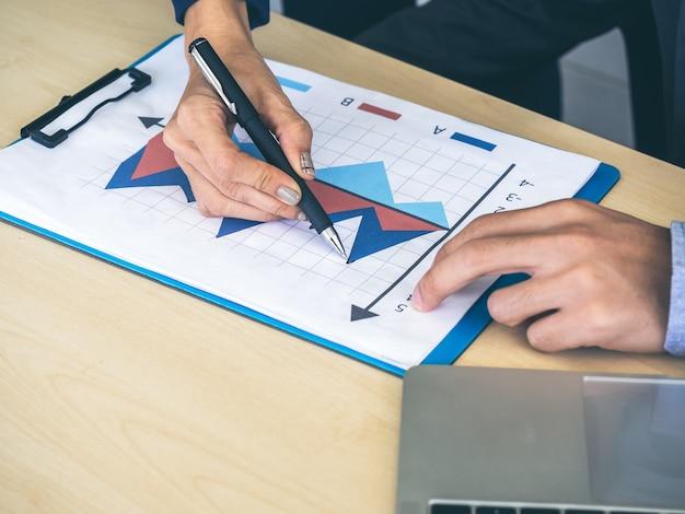 Geschäftsmann- und frauenhände unter verwendung des stiftes, der für das überprüfen des berichtsdiagramms und des notizbuchcomputers auf holztisch zeigt, treffen und zusammenarbeiten im büro.